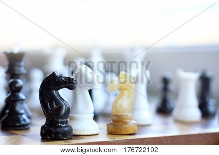 Three chess horses of different colors stand on the background of silhouettes of other figures / diplomatic peace talks