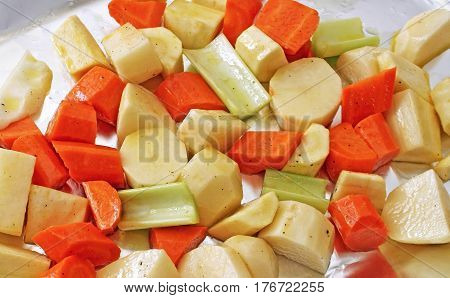 Potatoes, carrots, parsnips and celery seasoned with pepper and drizzled with oil ready for roasting