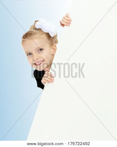 Beautiful little blonde girl dressed in a white short dress with black sleeves and a black belt.The girl peeks out from behind white banner.Close-up.On the pale blue background.