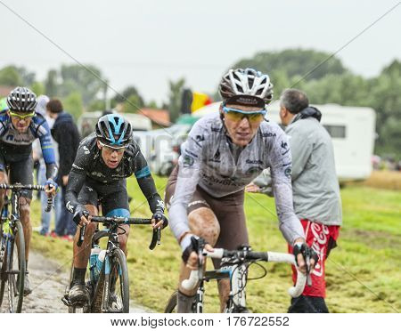 Ennevelin France - July 092014: The Australian cyclist Richie Porte ( Sky Team) behind Romain Bardet (AG2R La Mondiale Team) riding on a cobbled road during the stage 5 of Le Tour de France 2014.