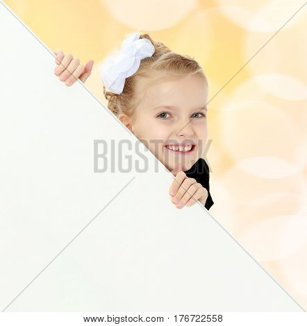 Beautiful little blonde girl dressed in a white short dress with black sleeves and a black belt.The girl peeks out from behind white banner.Close-up.