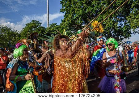 RIO DE JANEIRO, BRAZIL - FEBRUARY 28, 2017: Musician woman covered with tinsel playing trombone on the background of other costumed musicians at Bloco Orquestra Voadora in Flamengo Park, Carnaval 2017
