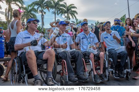 RIO DE JANEIRO, BRAZIL - FEBRUARY 28, 2017: Four disabled man in wheelchair distributing leaflets of Lei Seca during Bloco Orquestra Voadora in Flamengo Park, Carnaval 2017