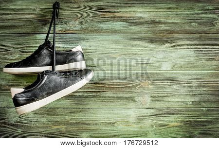 Black sneakers with a white sole hanging on a turquoise wooden background background