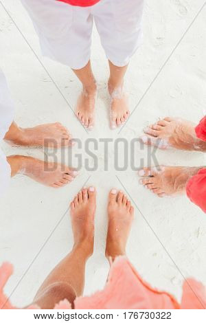 Top view image of feet of family standing on the white sand beach.