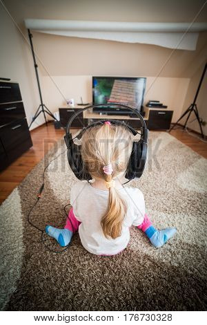 girl with headphones on her head. She is watching tv