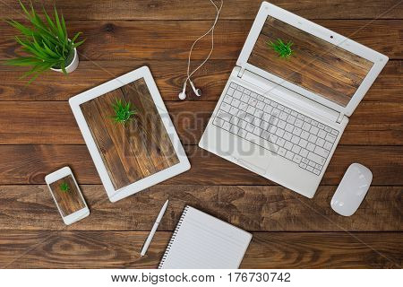 Responsive Design Theme Example different Electronic Gadgets Computer Tablet and Telephone with same Image on screen on wood handcrafted table