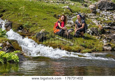 Rapid clean creek vivid colors rocks two young people making stop to relax and drink water