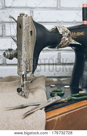The handwheel vintage sewing machine. Black retro sewing machine on brick background. Scissors on a wooden support