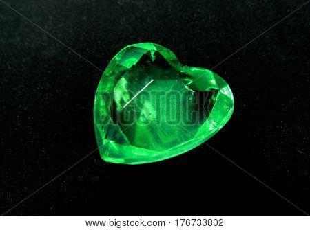emerald gem heart on black background love concept