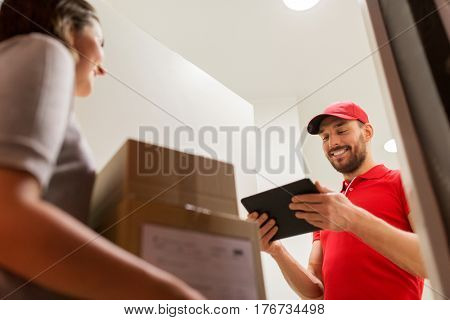 delivery, mail, people and shipping concept - happy man with tablet pc computer and customer with parcel boxes at home