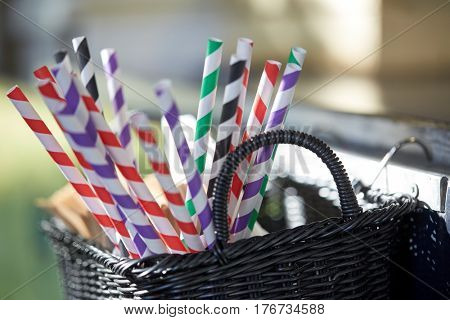 dishware and eating concept - disposable straws in whickered basket outdoors