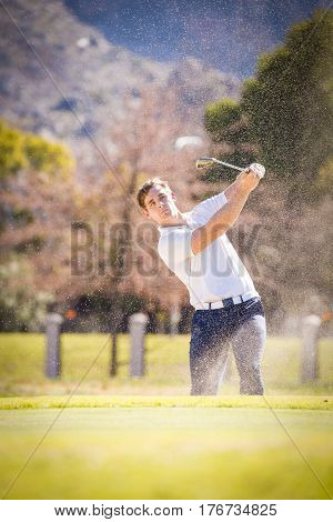 Close Up Image Of A Golfer Playing A Chip Shot Onto The Green On A Golf Course In South Africa.