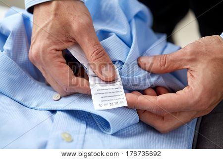 clothes, housework, laundry and people - male hands holding shirt and label with washing instruction