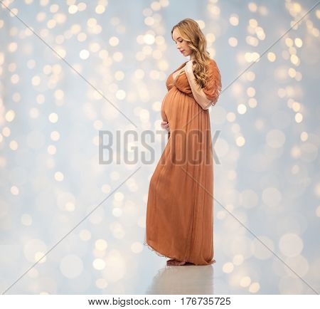 pregnancy, motherhood, people and expectation concept - happy pregnant woman touching her big belly over holidays lights background