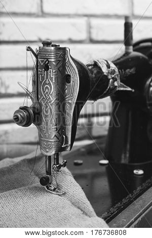 The handwheel vintage sewing machine. Black retro sewing machine on brick background. Wooden support. Black and white