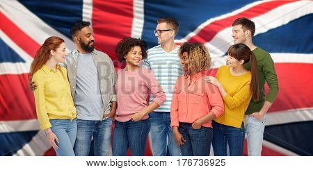 diversity, race, ethnicity and people concept - international group of happy smiling men and women over british or english flag background