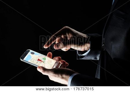 business, location, people and future technology concept - close up of businessman hands with transparent smartphone with gps navigator map on screen over black background