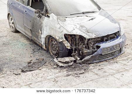 burned blue car in the street, broken window