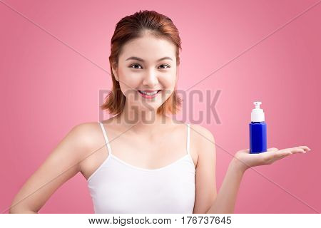Woman Use Body Lotion On Arms And Holding Cosmetics Bottle On Pink Background.