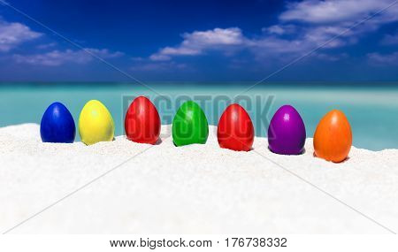 Colorful easter eggs in a row on a tropical beach