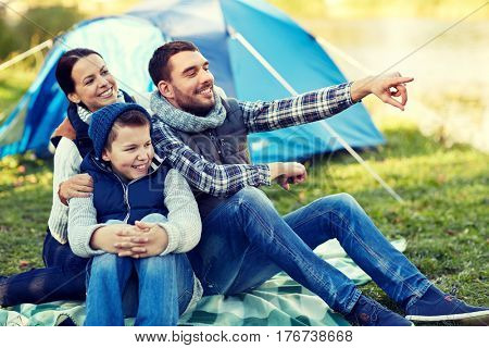 camping, tourism, hike and people concept - happy family over tent at camp site pointing finger to something