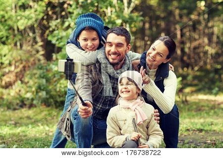 travel, tourism, hike, technology and people concept - happy family taking picture with smartphone selfie stick in woods