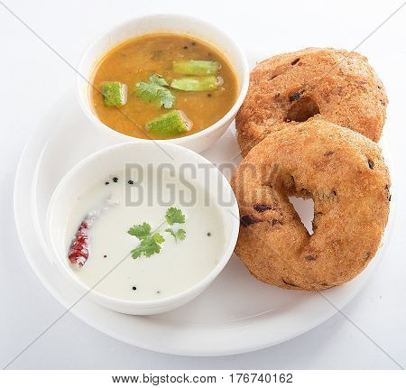 Delicious medu vada served with coconut chutney and sambar in a white plate