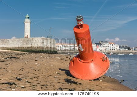Buoy at the entrance to the harbor of Saint-Gilles Croix de Vie with the tour Josephine on the background (Vendee, France)