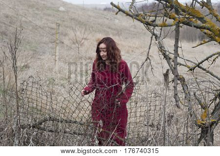 the girl in the red dress and the warmth of red hair on the verge of the rustic fence