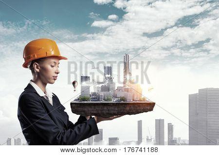 Woman presenting construction model . Mixed media