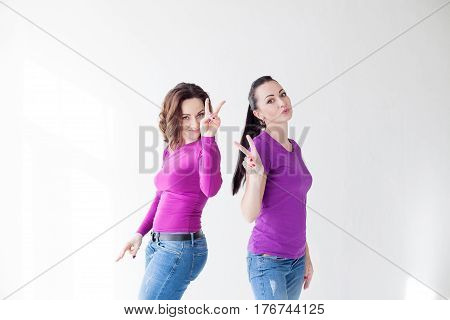 two women in purple clothes show fingers 2