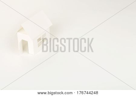 white cardboard house on white surface abstract house concept