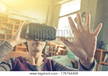 mature woman using vr headset in the house