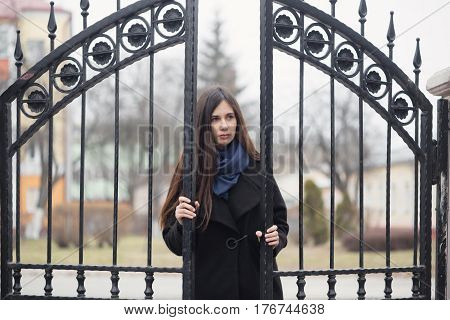 Portrait Of A Beautiful Girl Near The Wrought-iron Gate