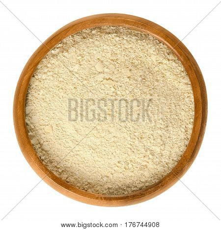 Nutritional yeast flakes in wooden bowl, made from deactivated dried yeast. Food product, used as an ingredient in recipes or as an condiment. Isolated macro food photo close up from above over white.