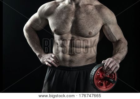 Muscular Bodybuilder Man Holds Wheel Trimmer For Six Pack