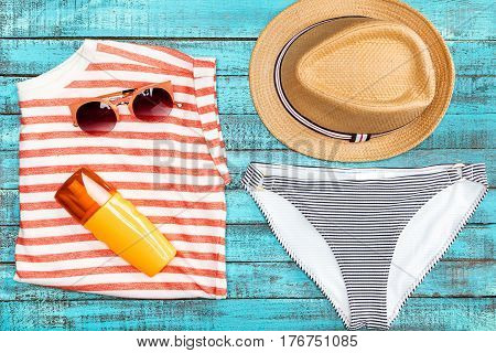 Top View Of Straw Hat, Bikini Bottom, Sunglasses And Sunscreen On Wooden Table, Summer Concept