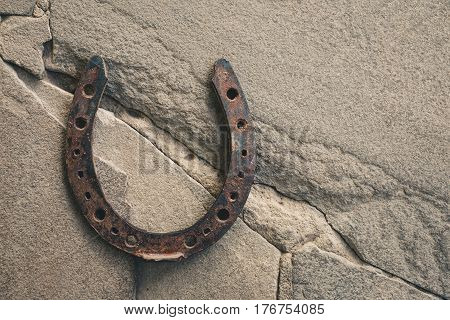 Old rusty horseshoe on natural stone background. Macro shot.