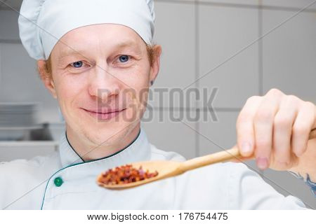 A man is going to cook a vegetarian. Healthy food. Different kinds of vegetables. The cook is trying food. Portrait of a smiling man.