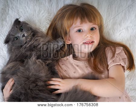 Child with a cat. Redhead little girl hugging a grey cat