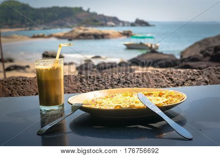 Breakfast on the ocean. Cocktail in a glass and scrambled eggs on a plate on the background of beach sea and sky.