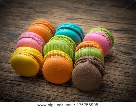 Colorful macarons on vintage pastel background. Macaron or Macaroon is sweet meringue-based confection.