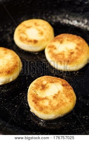Cheesecakes. Beautiful pancakes made of cheese in a black frying pan. Cheesecakes. Pancakes curd. Pancakes fritters, a traditional dish of Russia and Ukraine.