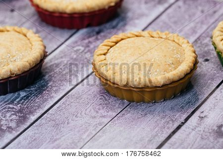 Apple pies of a round shape on a wooden table. close-up