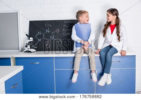 Little boy and girl in white coats chatting in chemical laboratory