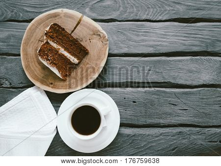 Piece of homemade cake and coffee on a black wooden table. Biscuit cake black coffee and napkin on a wooden table. Place for text