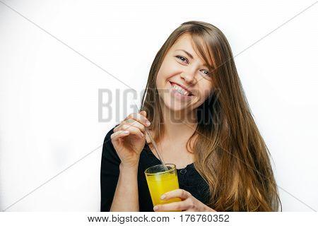 Young beautiful girl close-up portrait drinking orange juice. Female happy smile. Girl with orange juice on white background.