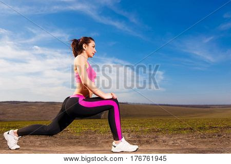 Young Woman Doing Exercises On Blue Sky Background