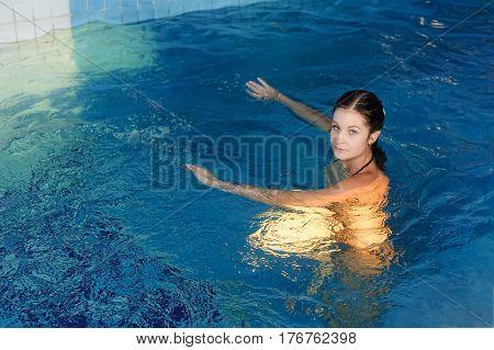 Portrait of beautiful woman in swimwear relaxing in swimming pool spa
